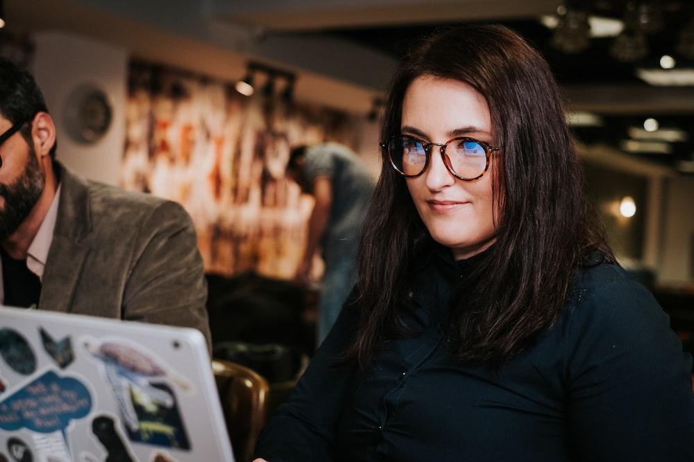 woman in black jacket wearing black framed eyeglasses
