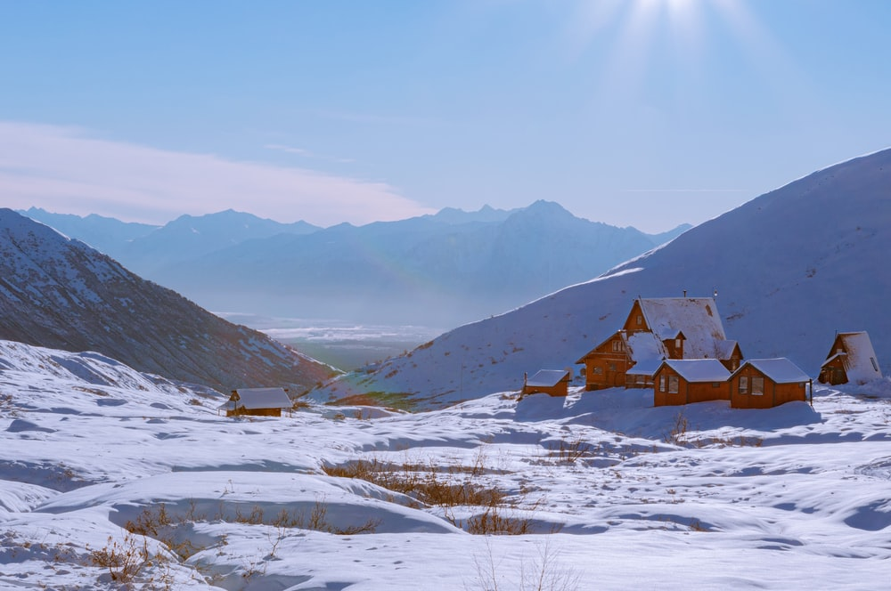 brown wooden house on snow covered ground near mountains during daytime