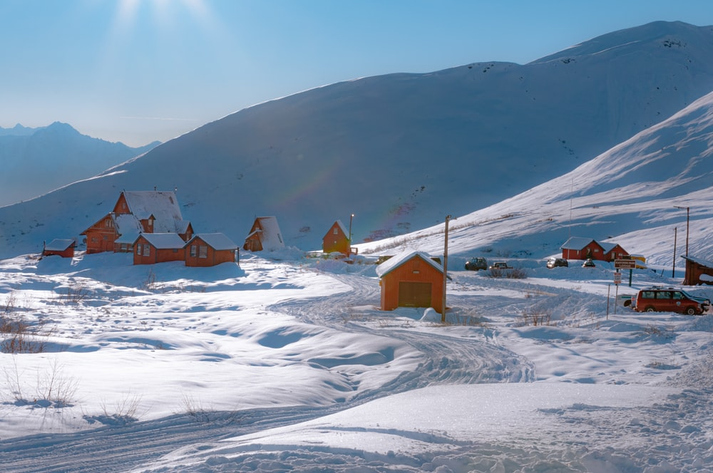 brown wooden houses on snow covered field during daytime