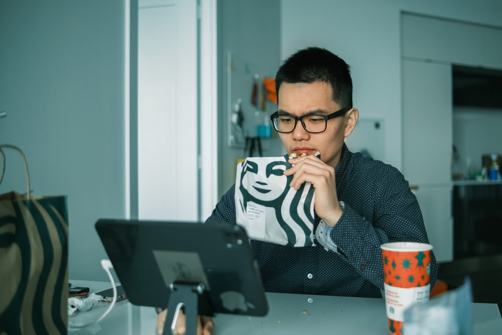 man in black and white sweater sitting beside black laptop computer