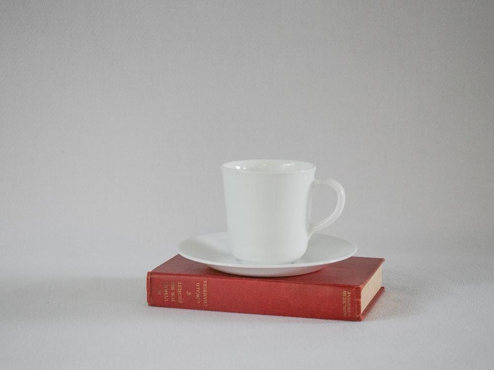 white ceramic mug on red book