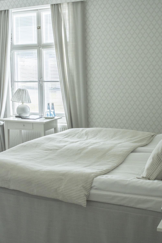 white bed linen near white wooden nightstand
