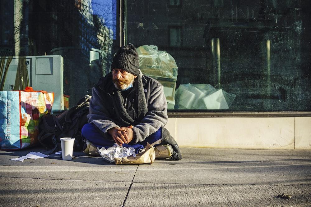 man in black and gray jacket sitting on sidewalk during daytime