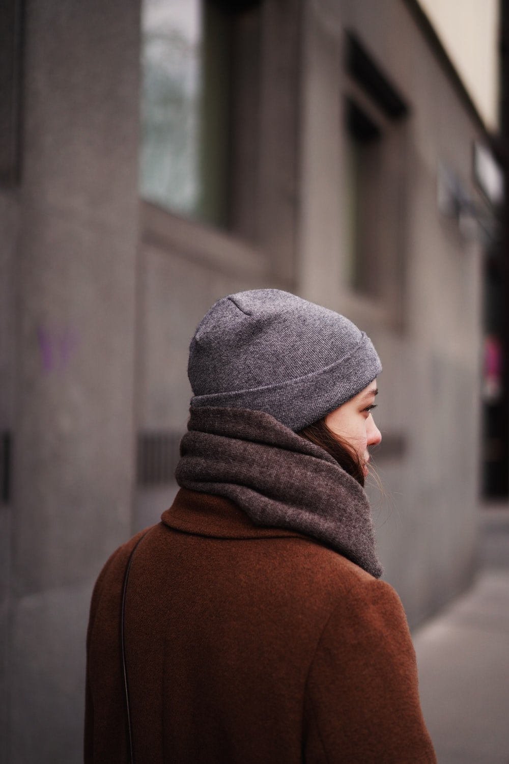 person in gray knit cap and brown hoodie