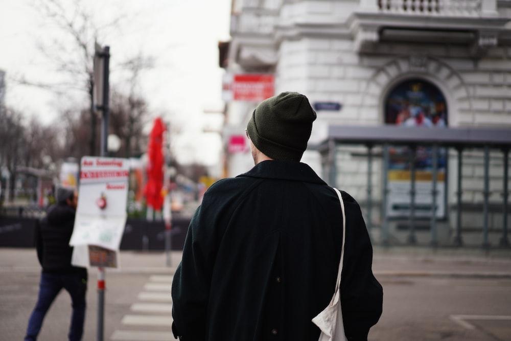 man in black hoodie standing on sidewalk during daytime