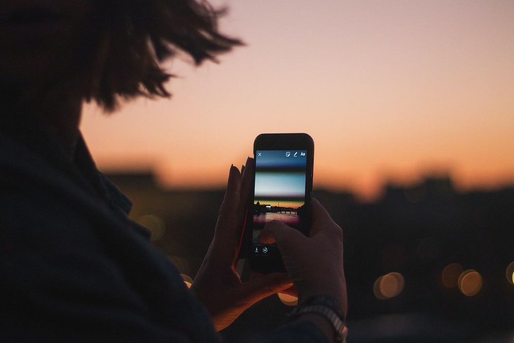person holding iphone 6 taking photo of sunset