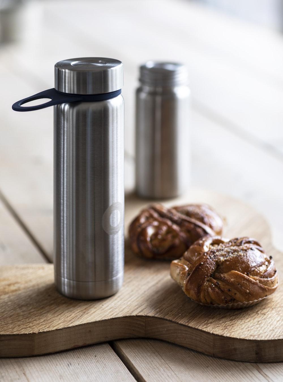 stainless steel vacuum flask beside brown cookies on brown wooden table