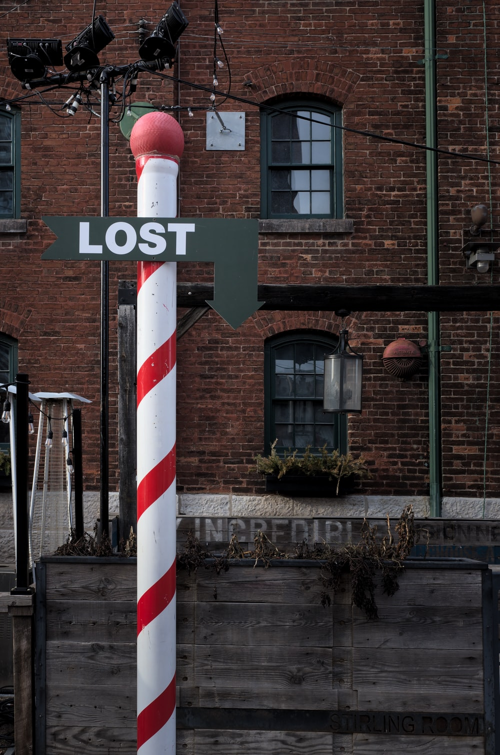 red and white striped post near brown concrete building