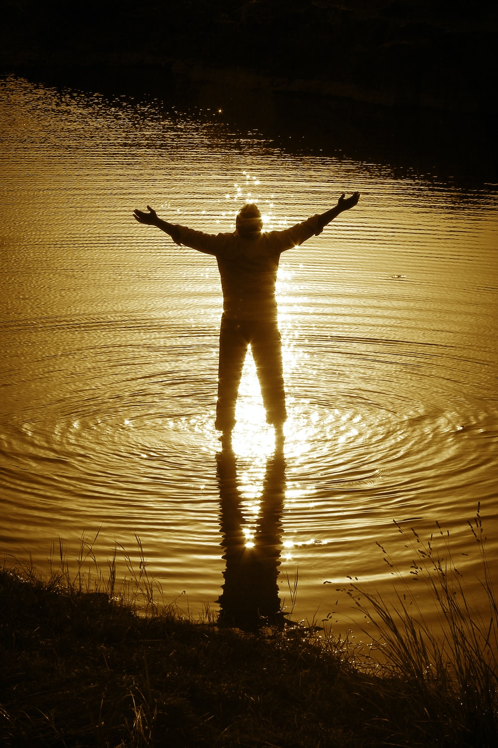 silhouette of person standing on water during daytime