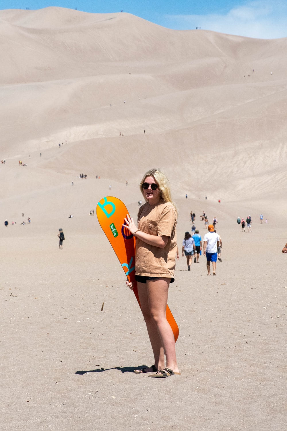woman in white shirt and blue denim shorts holding orange and yellow surfboard on white sand