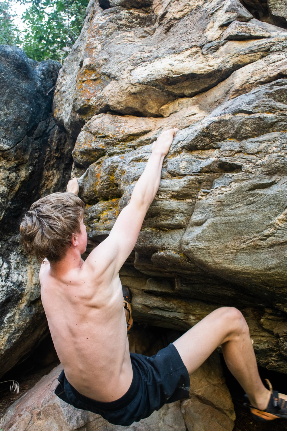 topless boy climbing on brown rock formation during daytime