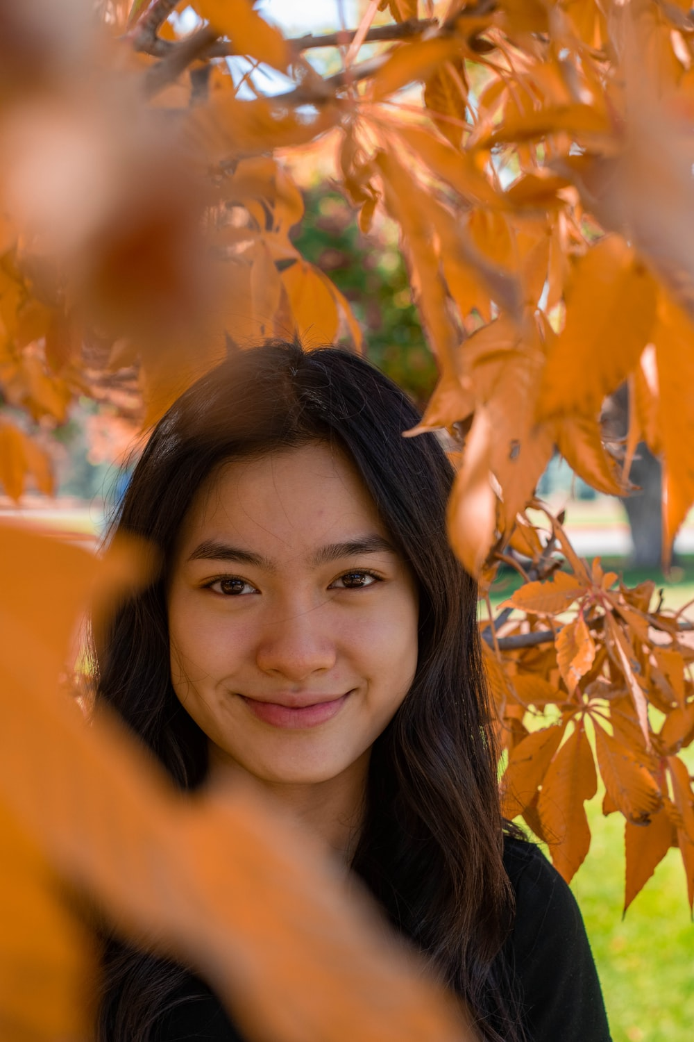 woman smiling near brown leaves during daytime