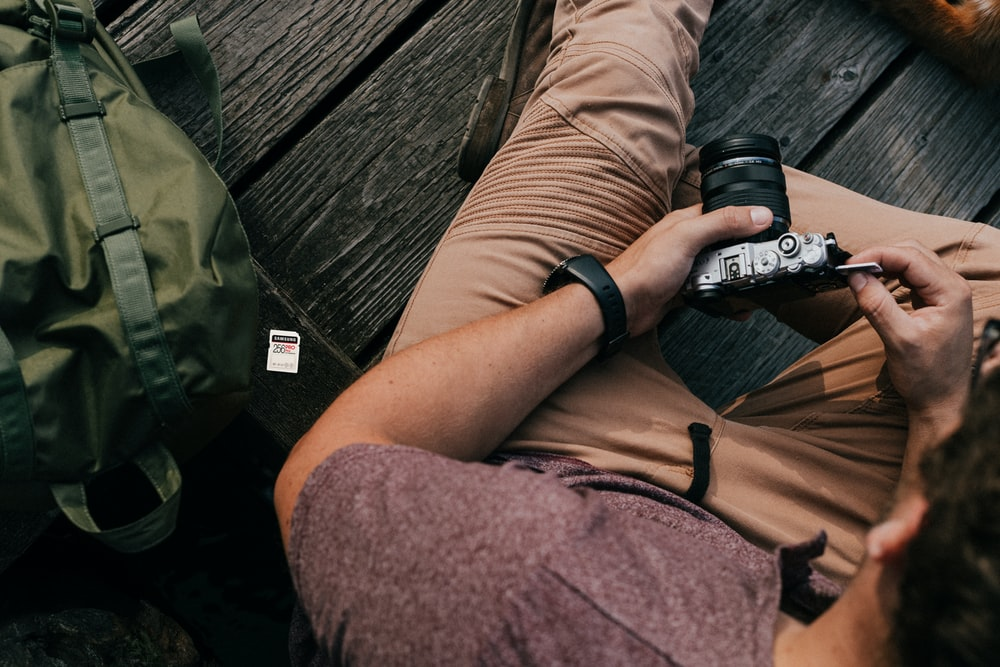 person in brown shorts holding black dslr camera