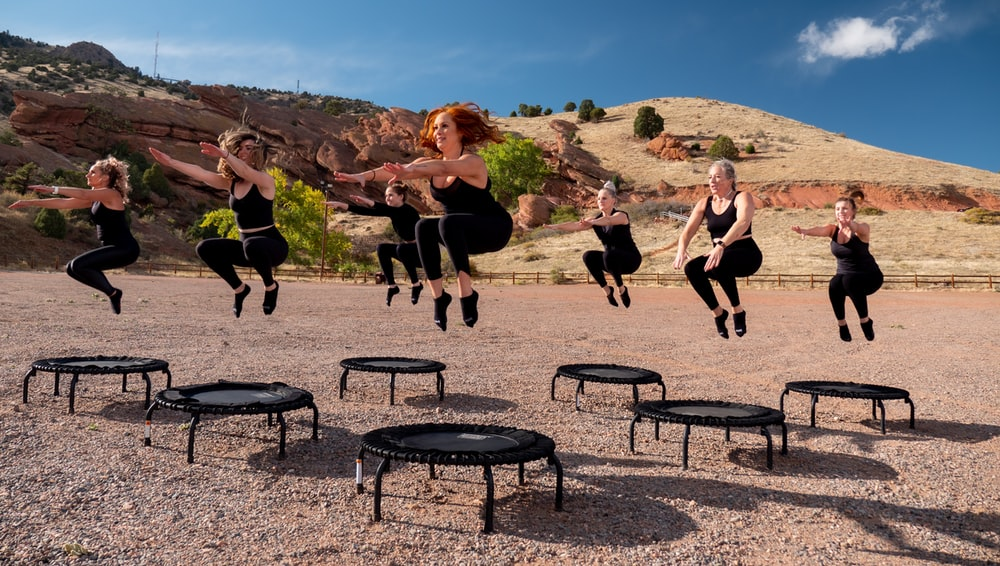 people sitting on black metal chairs on brown rocky mountain during daytime