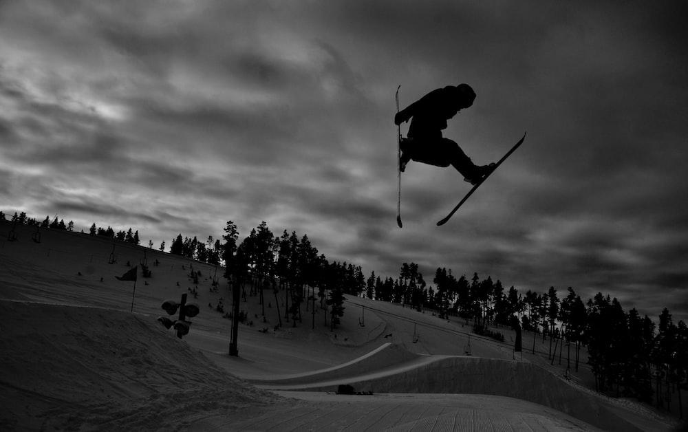 grayscale photo of people riding ski lift