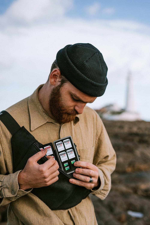 man in brown jacket holding black smartphone