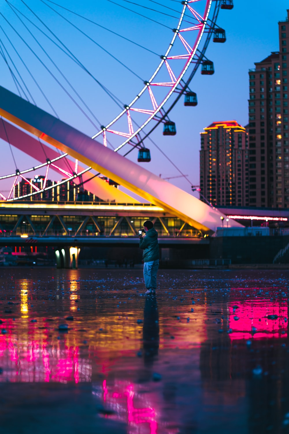 man in blue denim jeans standing on bridge during night time