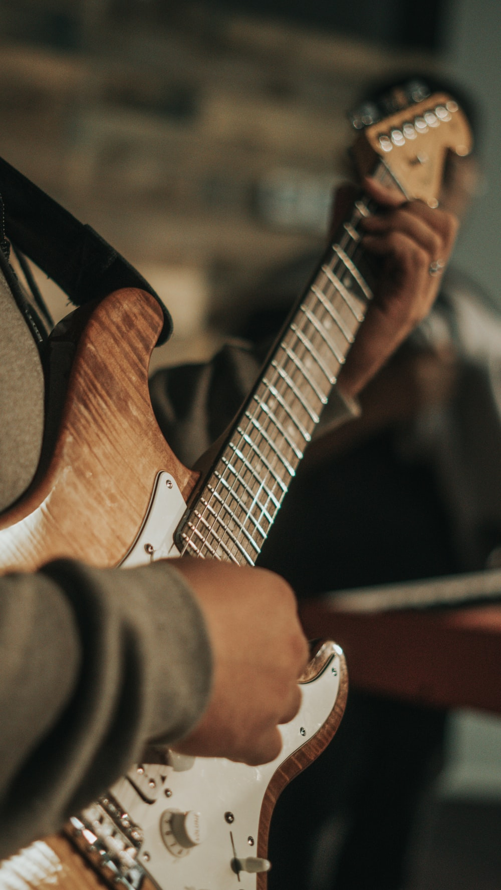 person playing brown and white electric guitar