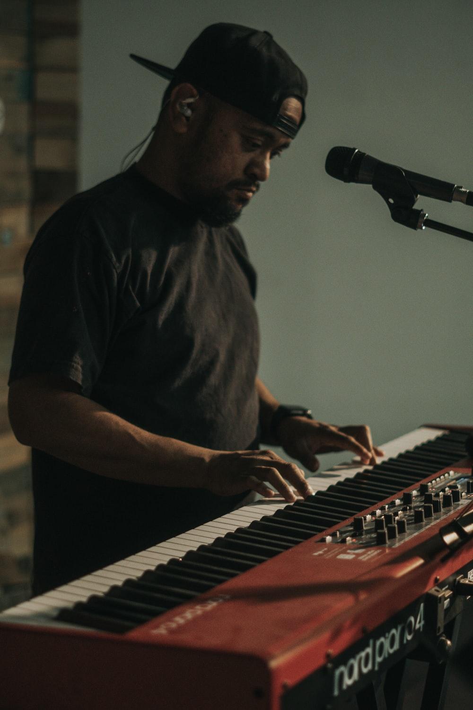 man in black button up shirt playing electric keyboard