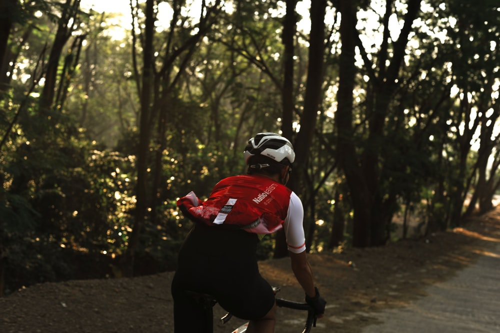man in red shirt riding bicycle