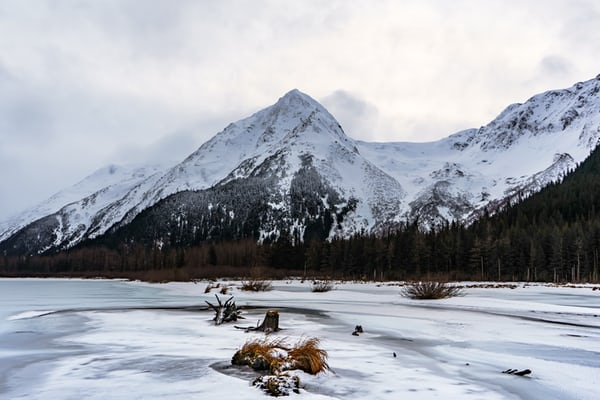 Snow covered moutnain behind a frozen lake