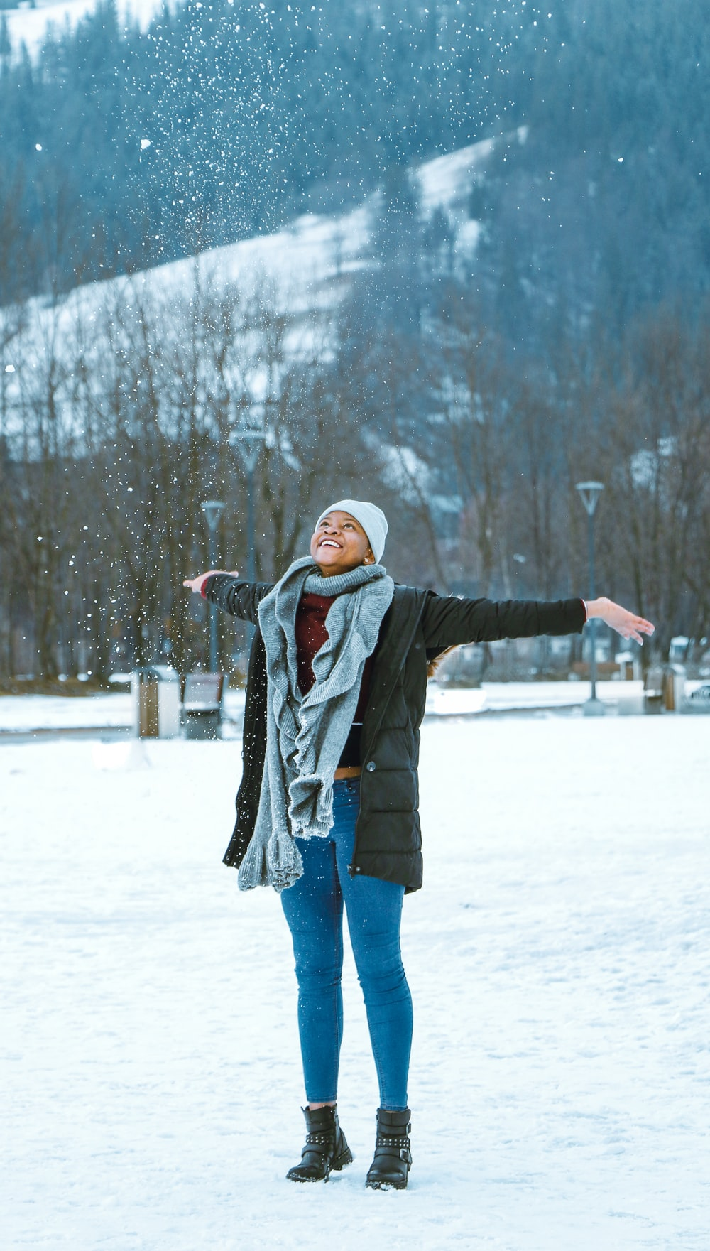 woman in black jacket and blue denim jeans standing on snow covered ground during daytime