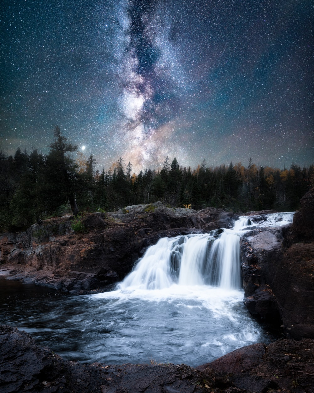 waterfalls near green trees under blue sky during night time