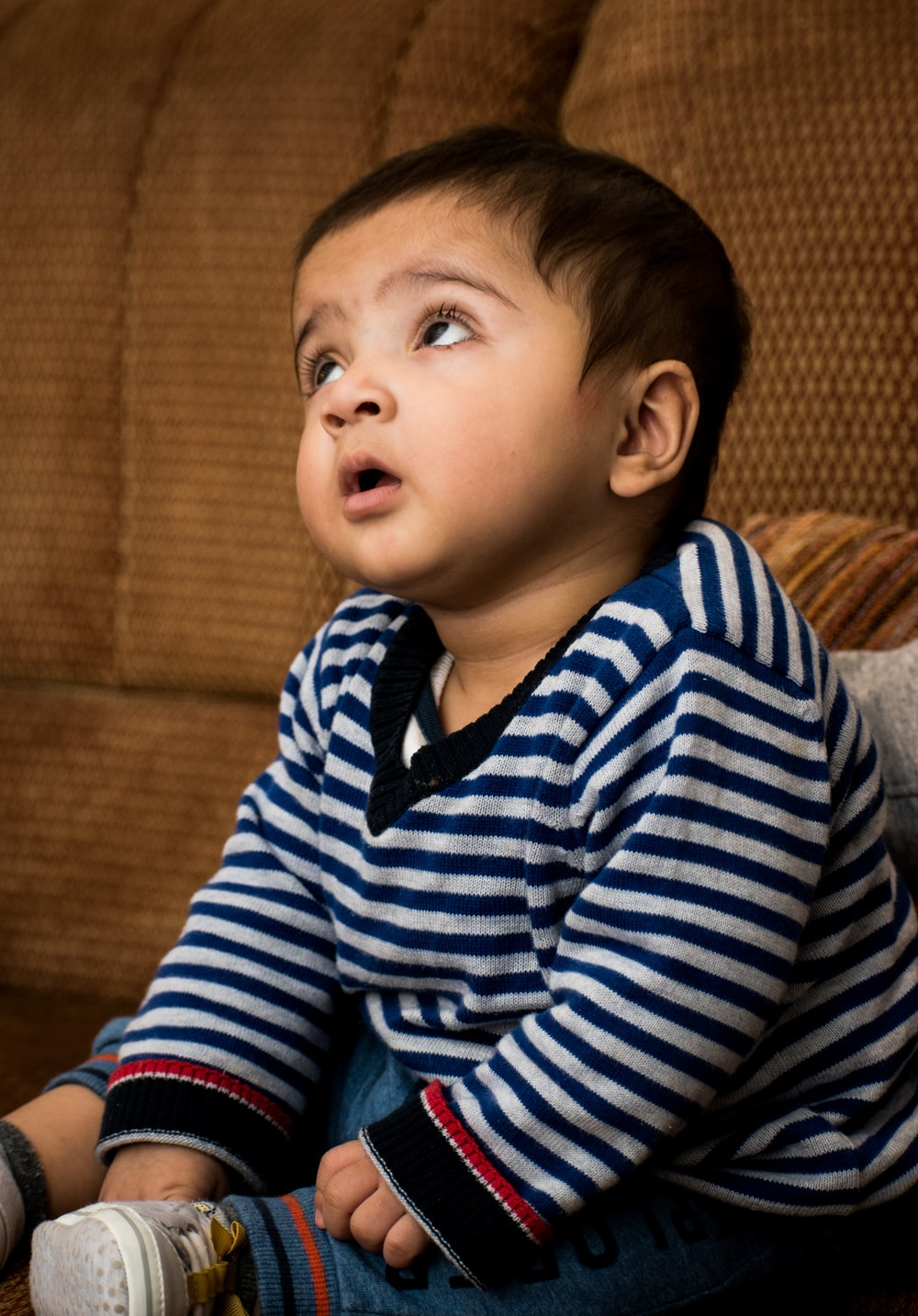 boy in blue and white striped long sleeve shirt sitting on brown sofa
