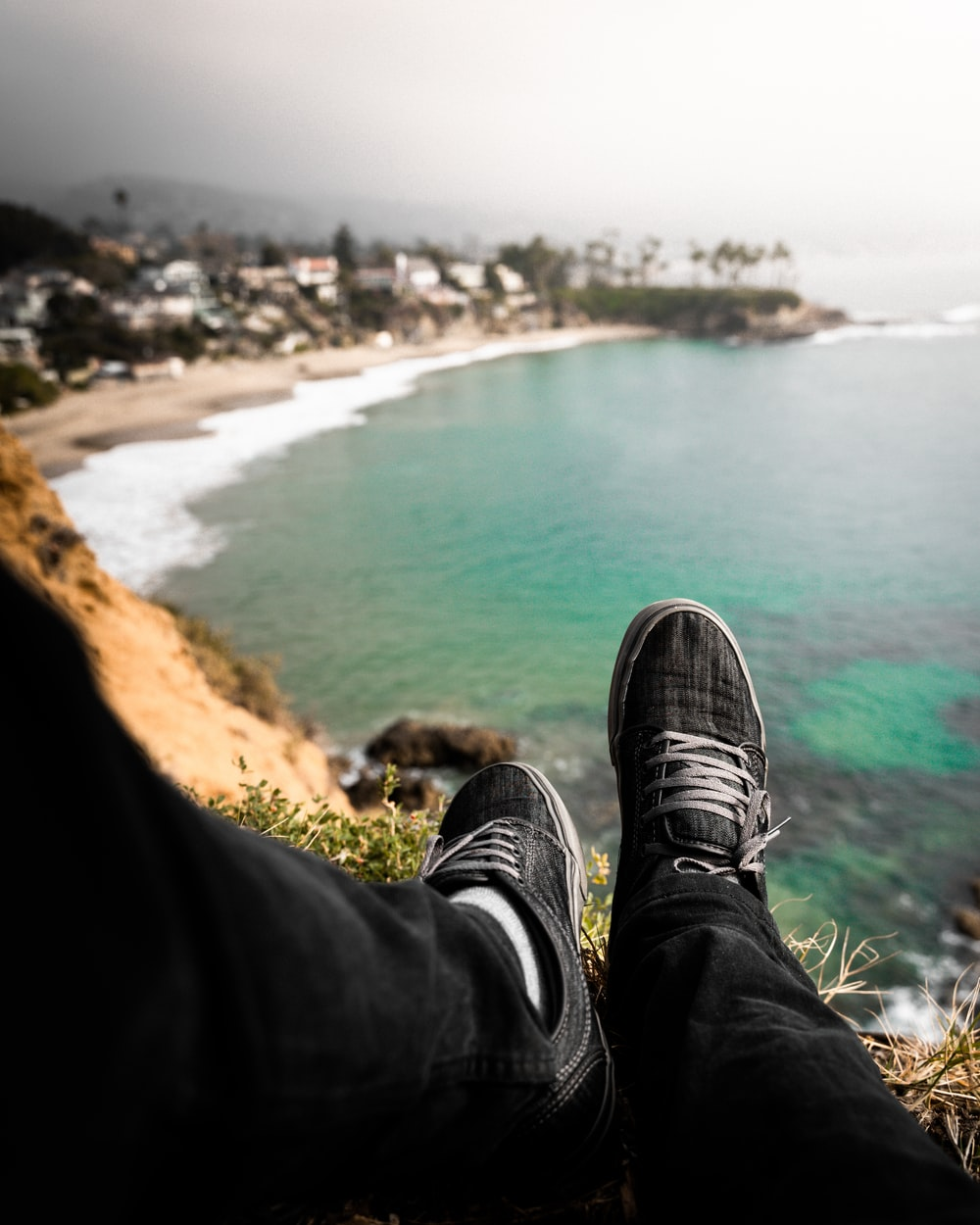person in black pants and black sneakers sitting on brown rock near body of water during