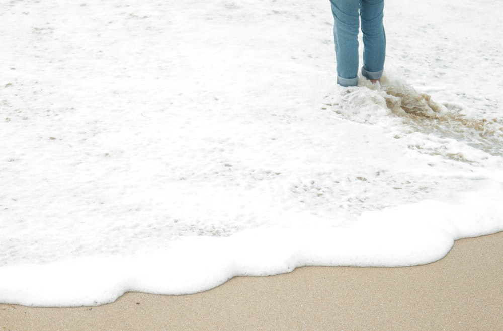 person in blue denim jeans standing on brown sand during daytime