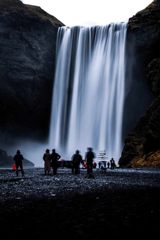people standing near waterfalls during daytime