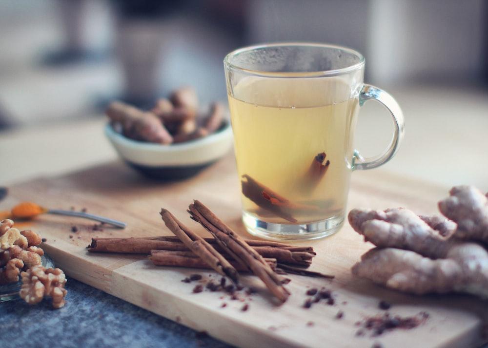 茶色の木製まな板に黄色の液体と透明なガラスのマグカップ