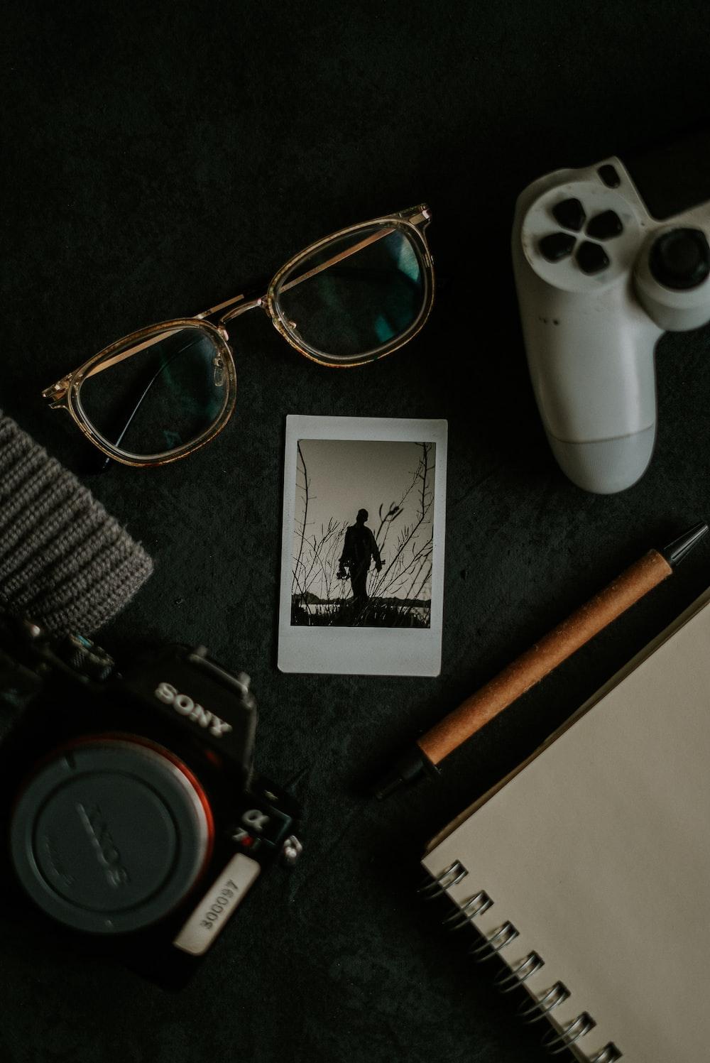 black and white sony dslr camera beside brown and black framed eyeglasses