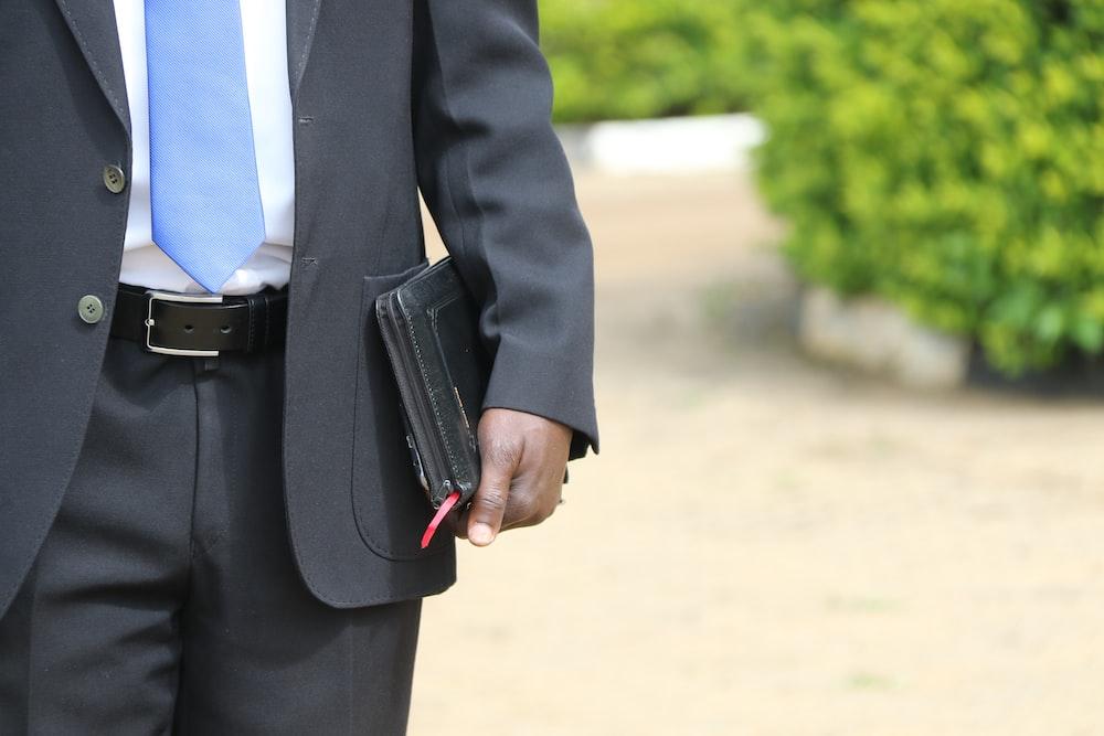 man in black suit jacket and black pants holding black leather bag