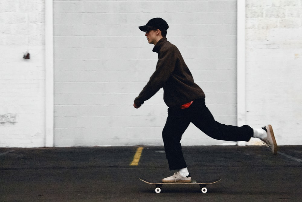 man in black pants and brown jacket riding skateboard