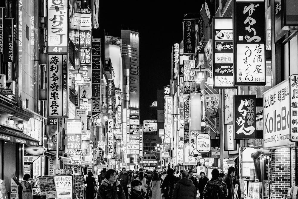 grayscale photo of people walking on street between high rise buildings