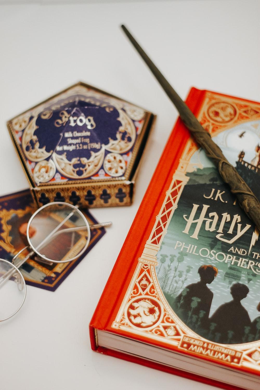 brown and black book beside eyeglasses