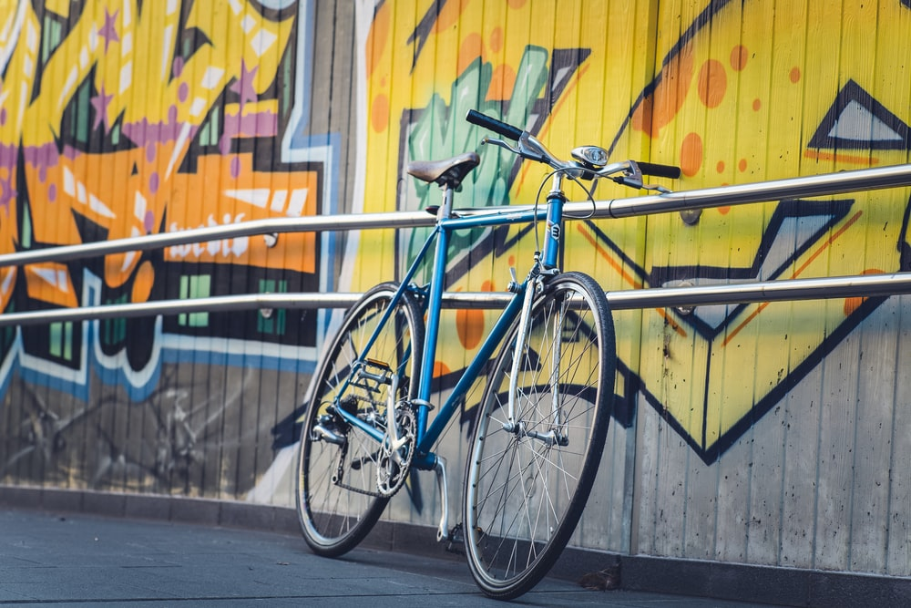 blue city bike parked beside blue metal fence during daytime