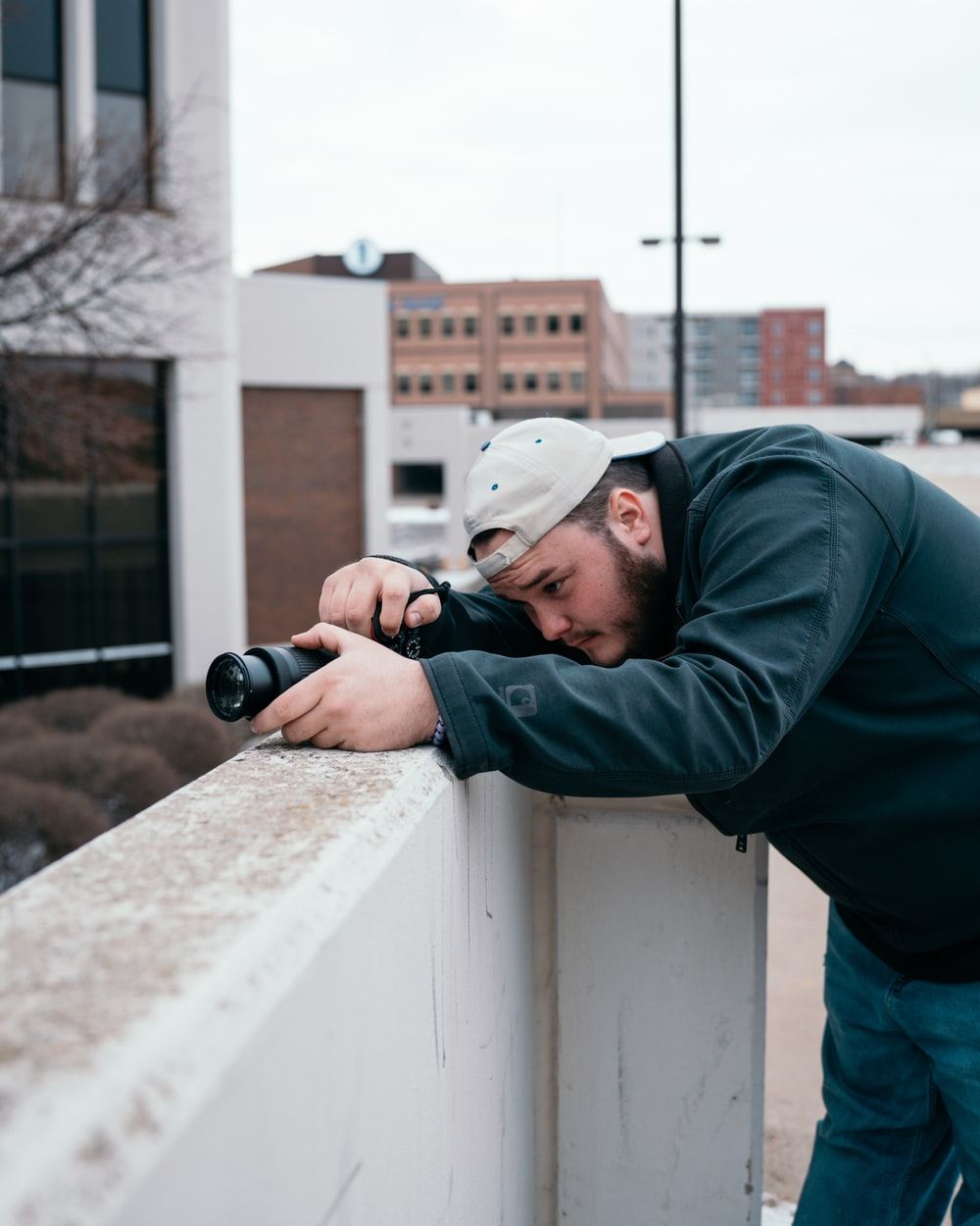 man in green hoodie holding black dslr camera