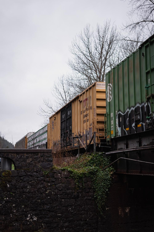green and brown train on rail tracks