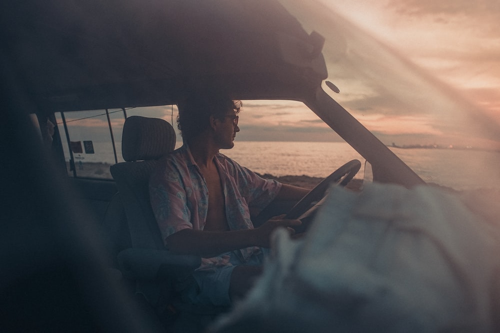 man in blue button up shirt sitting on car seat during sunset