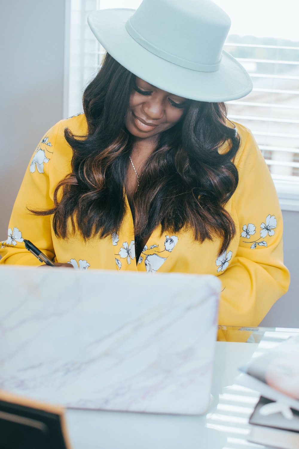 woman in yellow and black floral long sleeve shirt wearing white hat