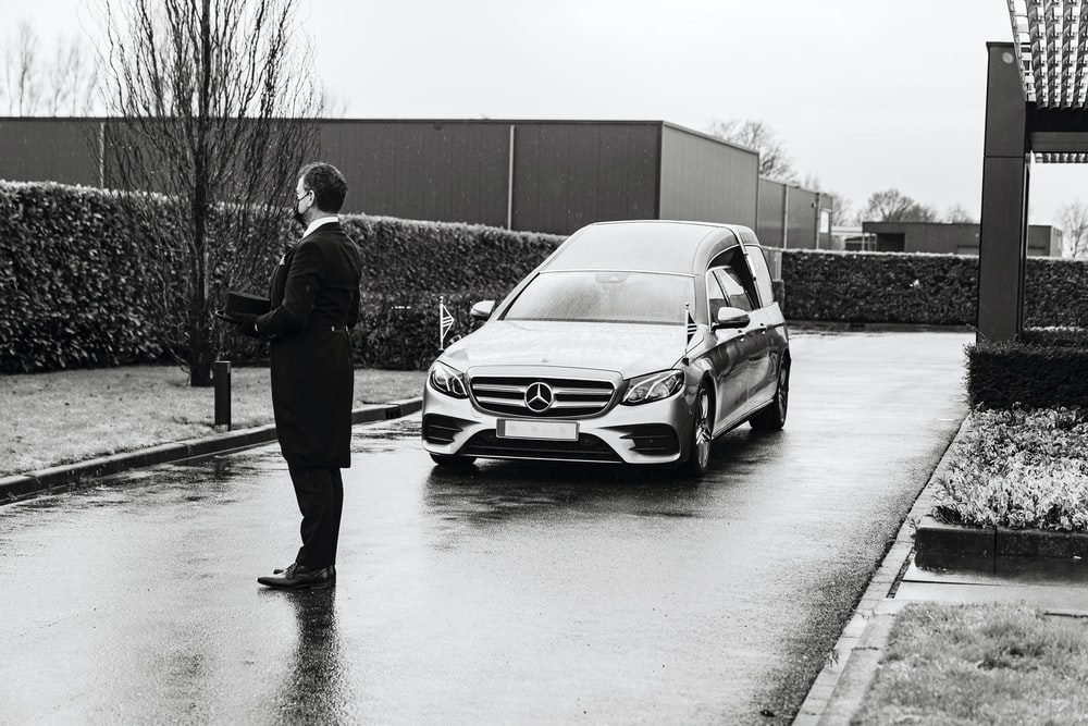 man in black jacket standing beside silver mercedes benz car