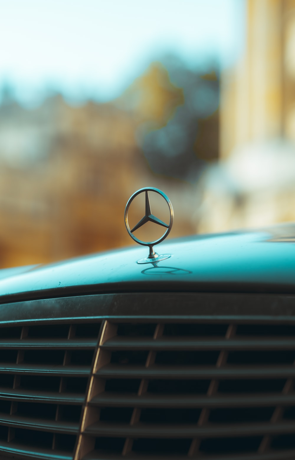 silver mercedes benz car with black and brown heart shaped emblem
