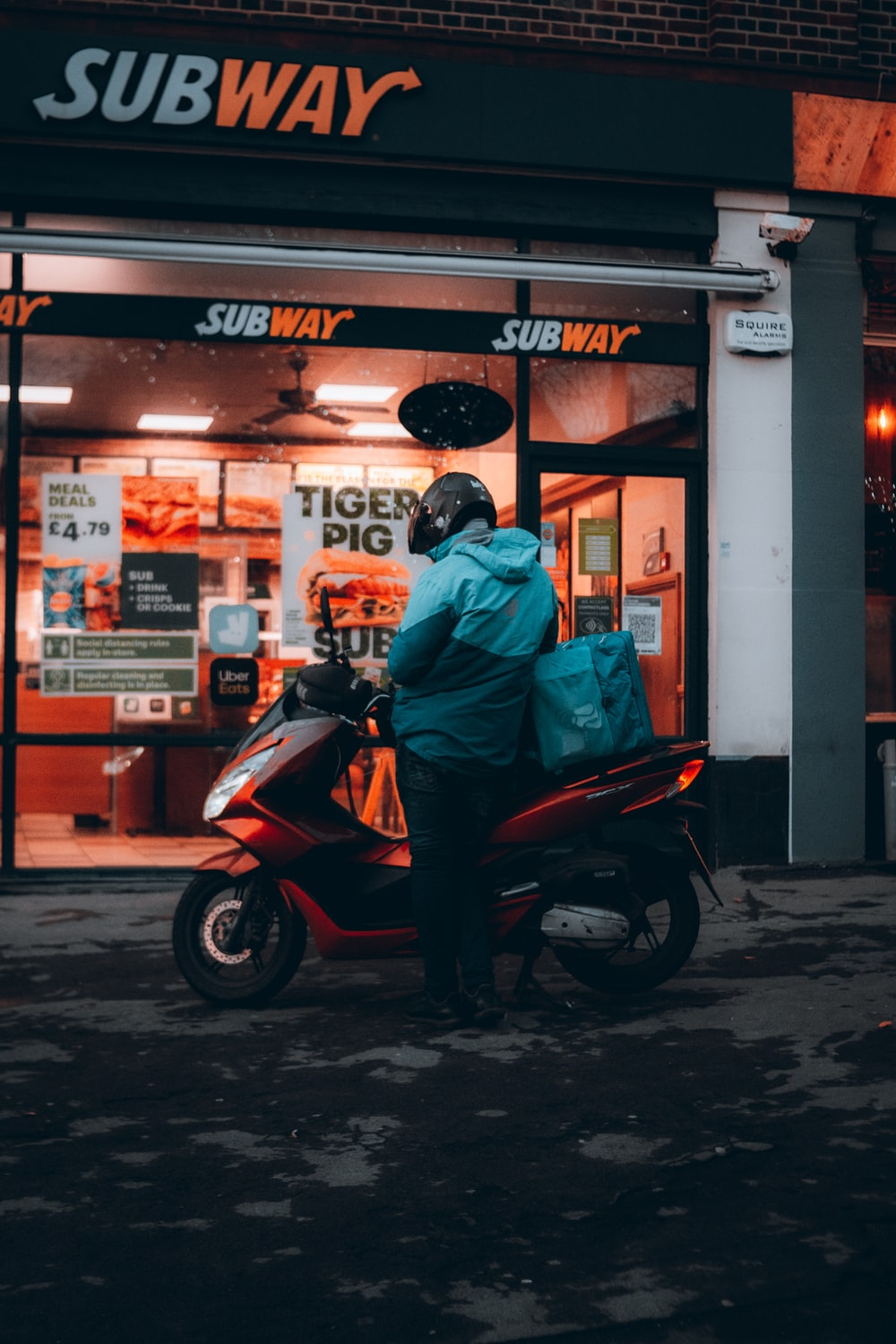 man in green jacket sitting on red and black motor scooter