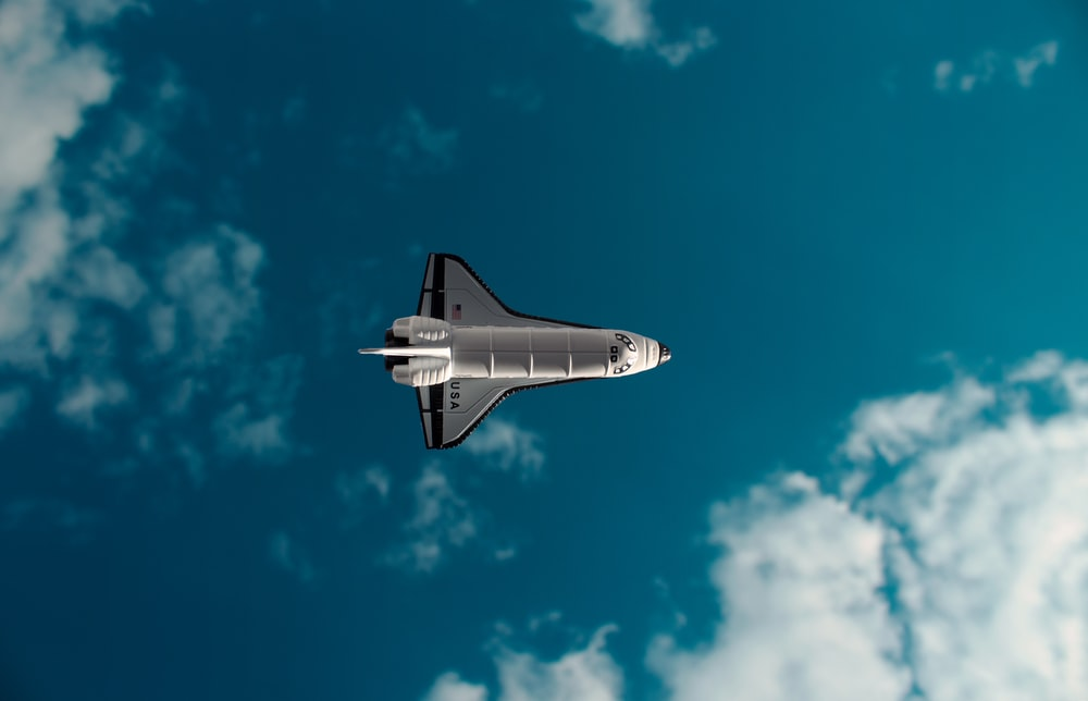 white and black jet plane in mid air under blue sky during daytime