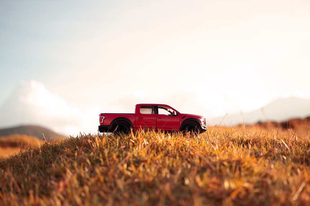 red single cab pickup truck on brown grass field