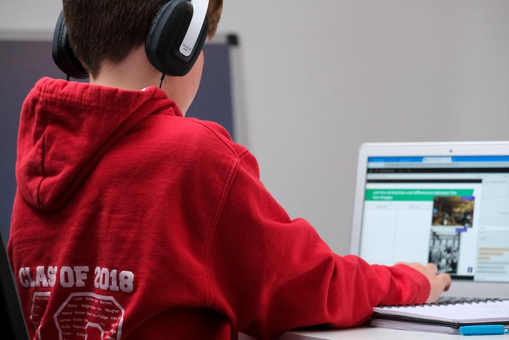 boy in red hoodie wearing black headphones