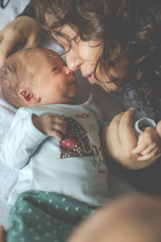 woman in gray crew neck shirt beside baby in gray onesie