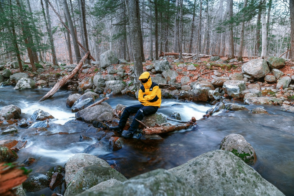 man in yellow and black jacket sitting on rock in river during daytime